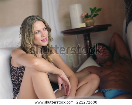 Couple relaxing next to bed - stock photo