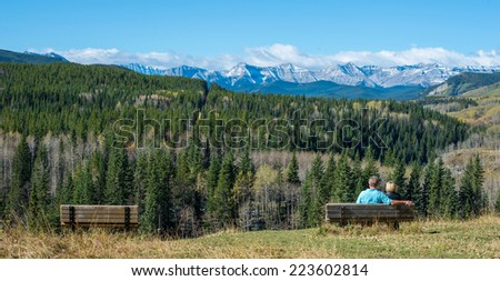 Couple relaxing on a bench overlooking autumn valley with mountains - stock photo