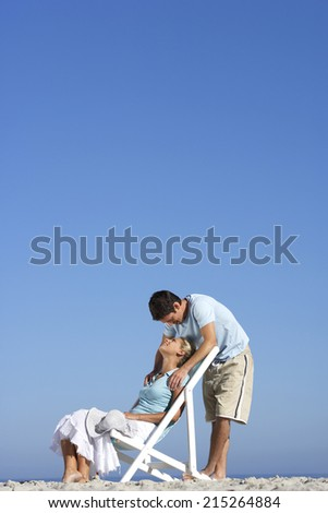 Couple relaxing on sandy beach, man standing behind woman in deckchair, side view - stock photo