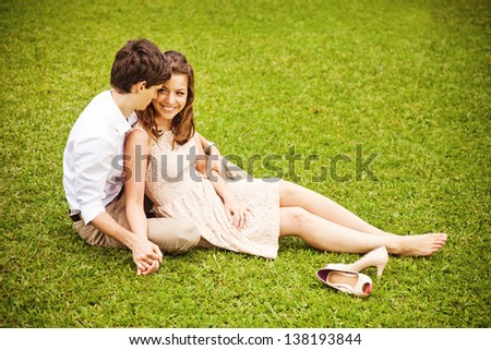 couple relaxing on the grass - stock photo