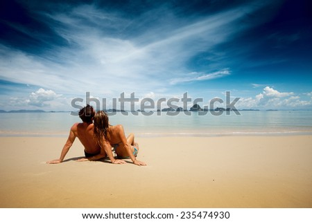 Couple relaxing on the tropical beach at sunny day