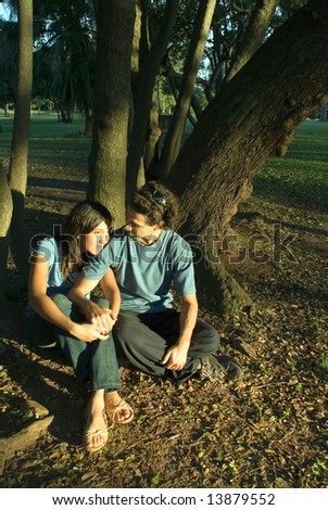 Couple relaxing under the trees. He is looking at her as she lays her head on his shoulder and they hold hands. Vertically framed photograph.