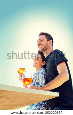 Couple relaxing while having spritz in a seafront - stock photo