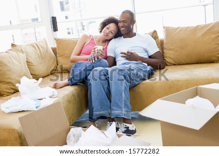 Couple relaxing with coffee by boxes in new home smiling - stock photo