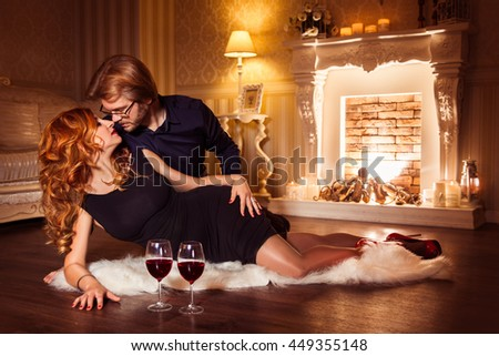 Couple relaxing with glass of red wine at fireplace background. Shot made in photo studio. Image toned. Horizontal. Image released.