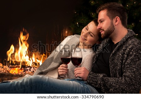 Couple relaxing with glass of wine at romantic fireplace on winter evening