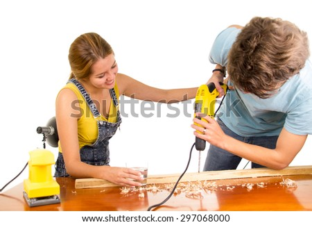 Couple renovating together as man using power drill on wooden surface with girlfriend standing beside him holding his back. - stock photo