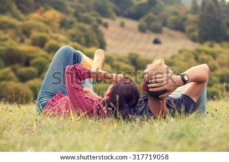 Couple rest in green grass on the hill in country side - stock photo