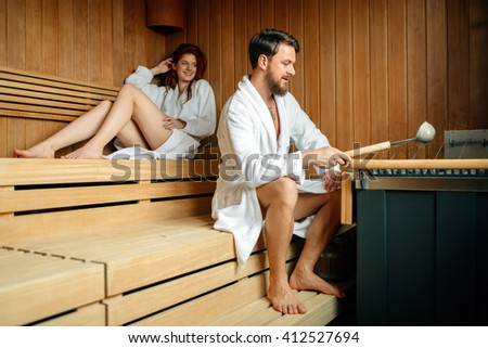 Couple resting and sweating in sauna - stock photo