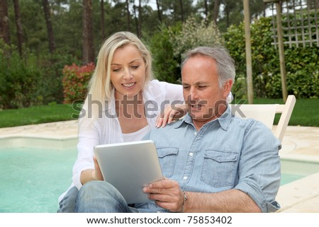 Couple resting in long chairs with electronic tablet
