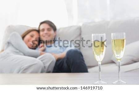 Couple resting on a couch with flutes of champagne on a coffee table - stock photo