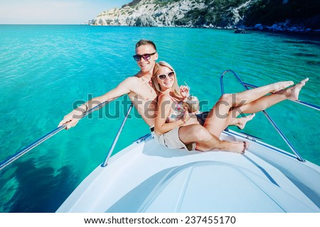 Couple resting on a yacht at sea. Luxury holiday vacation. - stock photo