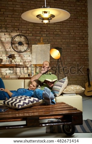 Couple resting on sofa at home, woman sleeping, man reading and yawning.