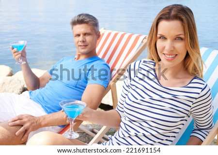 Couple resting together on the beach - stock photo