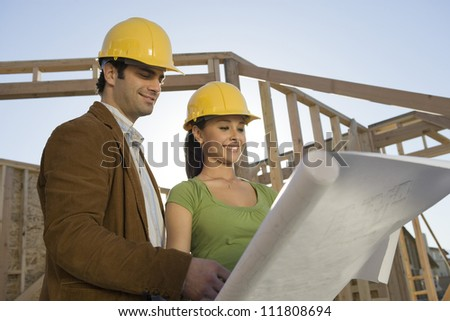 Couple reviewing blueprint at construction site - stock photo
