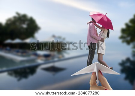 Couple ride paper plane on blur beach pool background - stock photo