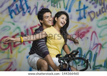 Couple riding a bicycle and smiling