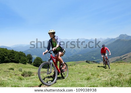Couple riding bicycles in the mountains - stock photo