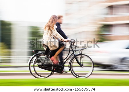 couple riding bikes in the city with motion blur - stock photo