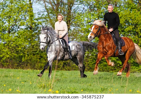 Couple riding horse in summer meadow.