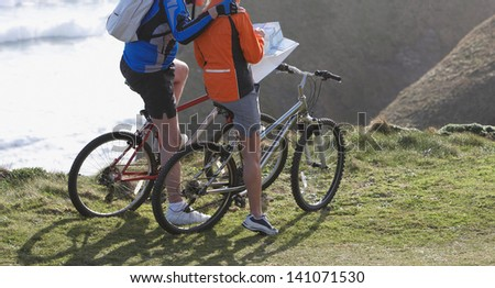 Couple riding looking at map on bike - stock photo