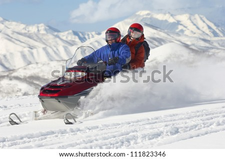 Couple riding motor sledge on a sunny day