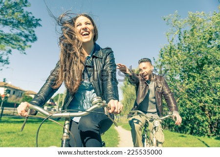Couple riding on bicycles  and having fun - Tourists driving around the city - Two friends riding on bikes in the countryside - stock photo