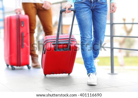Couple rolling large red suitcases, close up - stock photo