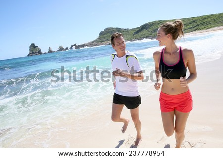 Couple runners exercising on a sandy beach - stock photo