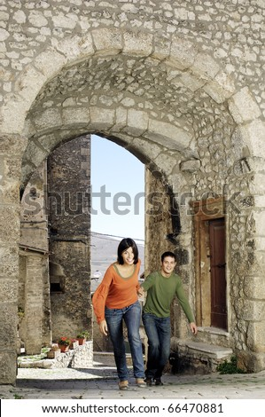 Couple runnin through the gate of an italian village