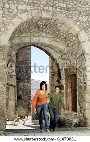 Couple runnin through the gate of an italian village - stock photo