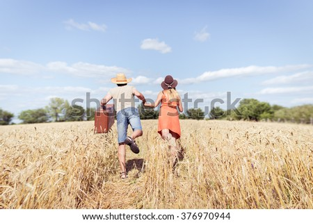 Couple running in field, man holding in his hand vintage suitcase on countryside landscape blue sky outdoors background. Vacation or immigration concept - stock photo