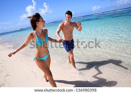 Couple running on a sandy beach - stock photo