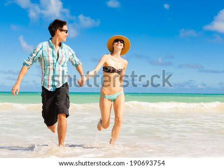 Couple running on a sandy beach. - stock photo