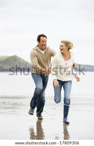 Couple running on beach holding hands smiling - stock photo