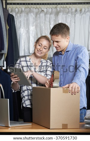 Couple Running On Line Clothing Store Packing Goods For Dispatch