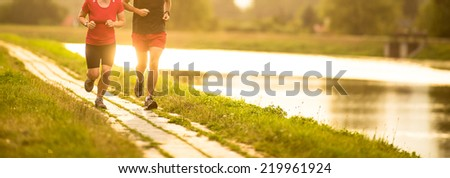Couple running outdoors, at sunset, by a river, staying active and fit (color toned image) - stock photo