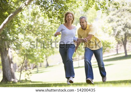 Couple running outdoors in park and smiling - stock photo