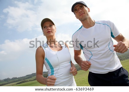 Couple running outside on a sunny day - stock photo