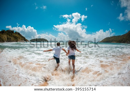 Couple running to the ocean