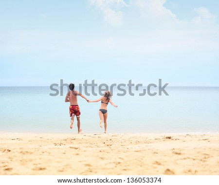 Couple running together into tropical sea - stock photo