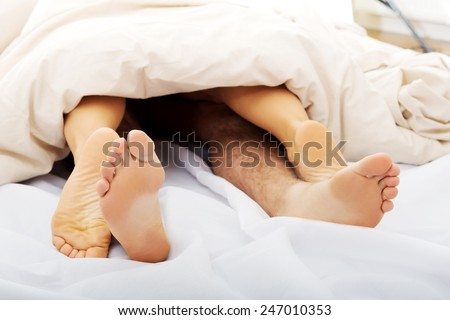 Couple's feet in bed under the quilt.