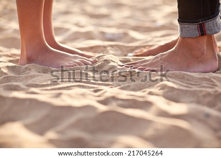 Couple's legs on the sand - stock photo