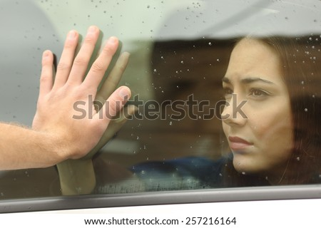 Couple saying goodbye before car travel holding hands through the window - stock photo