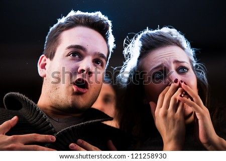 Couple scared at the cinema, watching horror movie,Italy