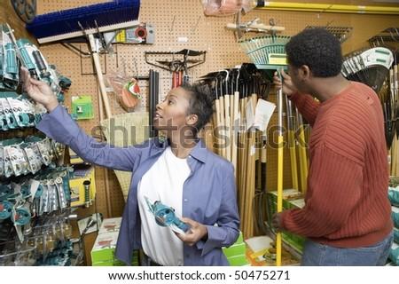 Couple selecting garden tools in shop - stock photo