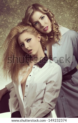couple sexy women with fashion blonde hair-style and make-up posing and smiling, wearing sensual open shirt in vintage color
