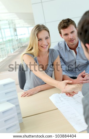 Couple shaking hand to real-estate agent in office - stock photo