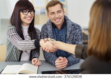 Couple shaking hands with their broker or insurance agent in her office smiling happily as they close a deal - stock photo