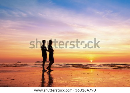 Couple sharing a romantic moment together on the beach at sunset - stock photo